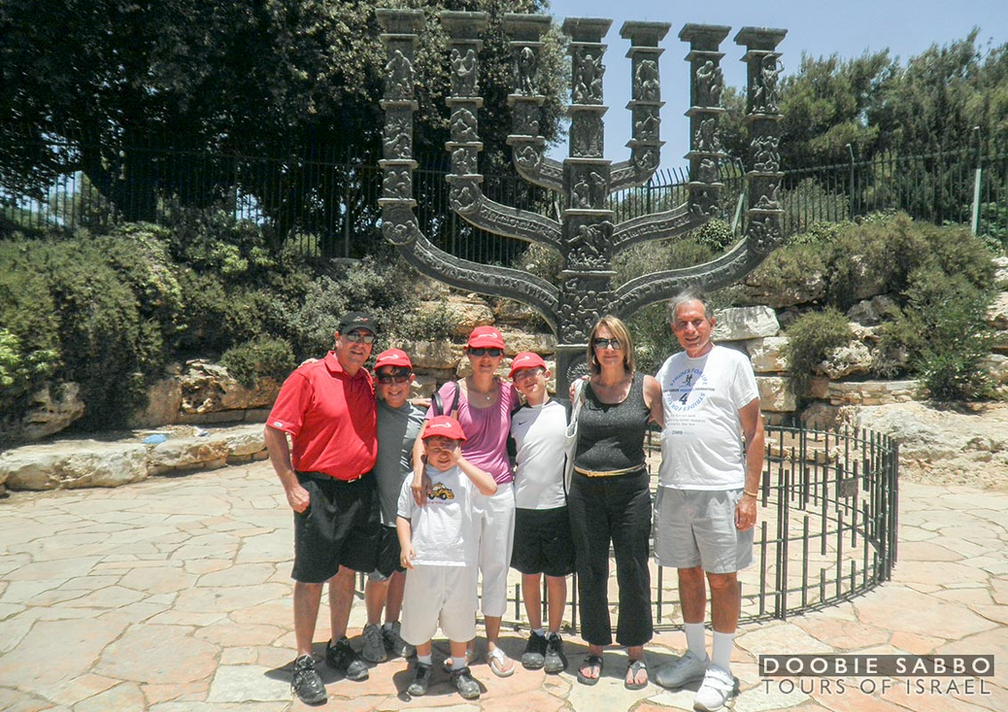 Family tour group in front of the Knesset Menorah.
